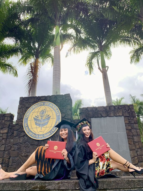 Two UH Hilo grads pose with their degrees