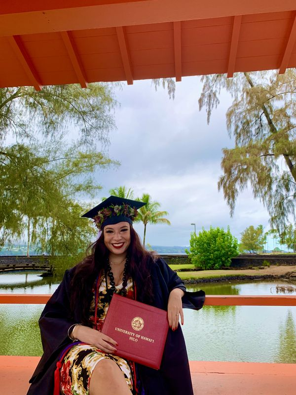 Alexandra Marie Cruz Koenig holding her degree at Liliuokalani park, with a big smile