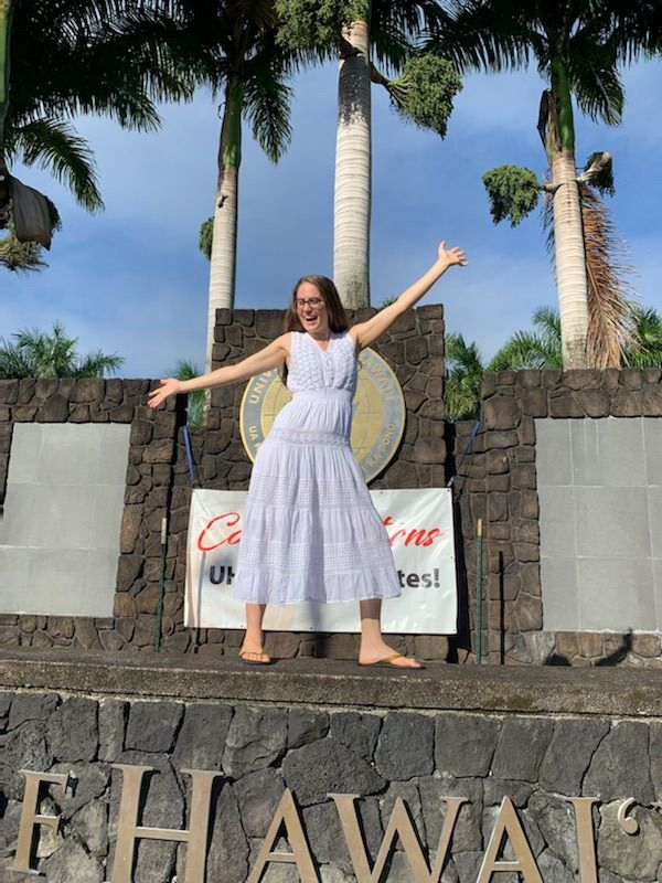 Kelsey May Meagher standing excitedly in front of the UH Hilo sign