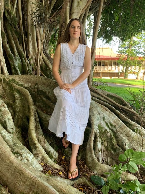Kelsey stands next to a giant banyan tree