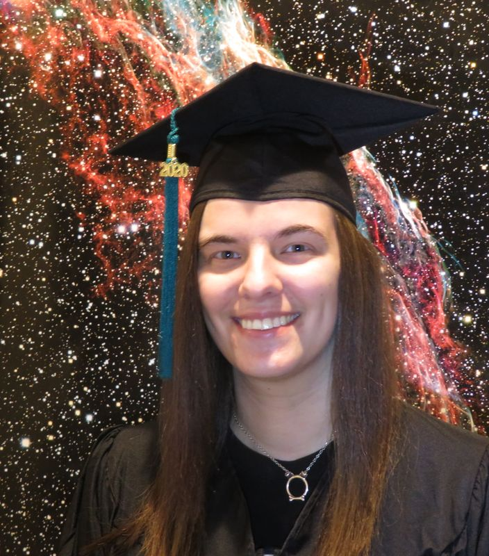 Kimberly Miskovetz smiles in a graduation cap, while posing against an image of a galaxy