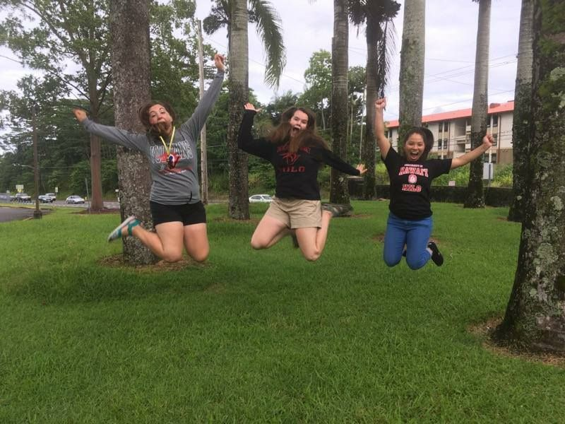 Three friends jump for joy on the lawn