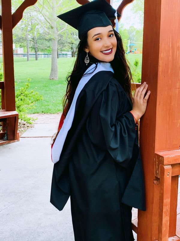 Alicia Avitia smiles while wearing a cap and gown