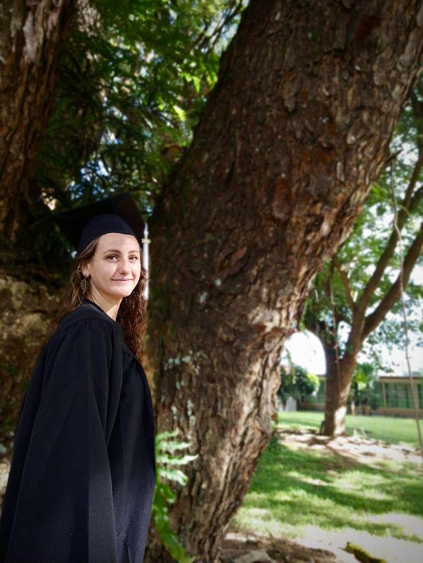 Cassandra stands next to a monkeypod trunk