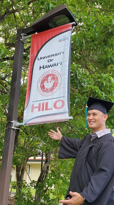 Victor M. Yurtola wears a cap and gown, gesturing toward the UH Hilo sign