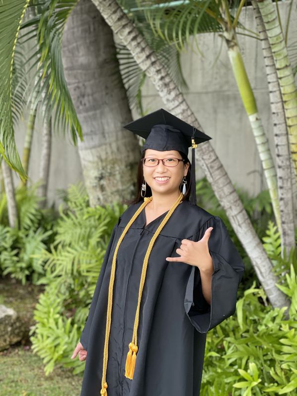 Anne Claire Masuda throws a shaka next to some palm trees