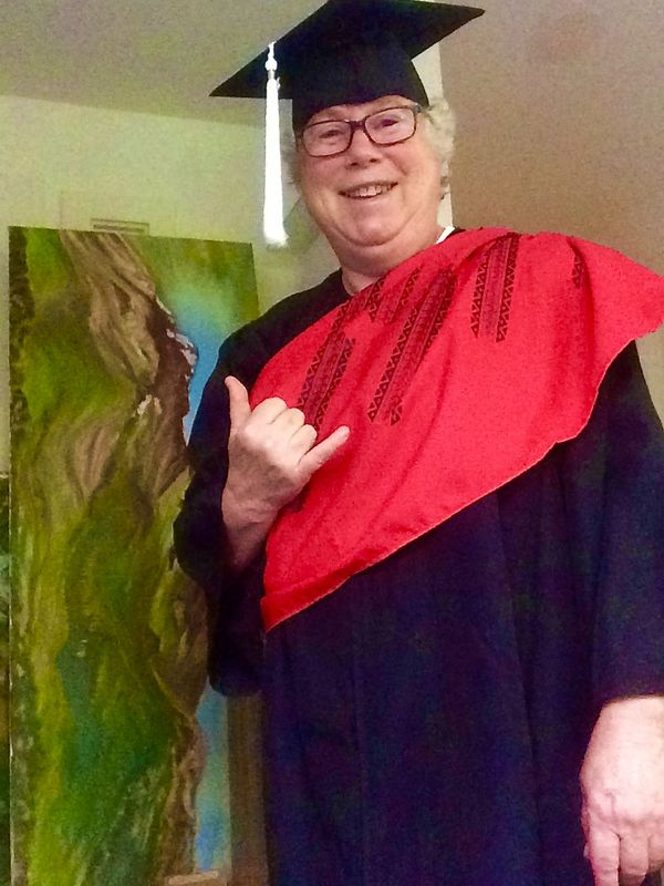 Victoria Anne Arthur throws a shaka while posing next to artwork and wearing commencement regalia