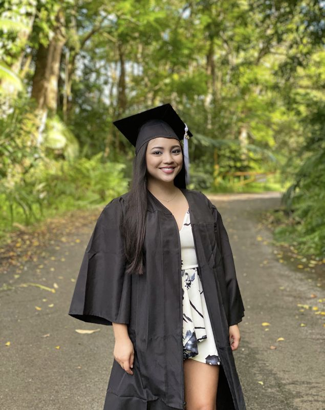Jessica Ranchez Valdez wearing graduation cap and gown and smiling