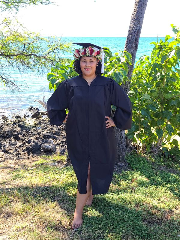 Bridget Ashley Endor with a flower-adorned graduation cap and UH Hilo mask