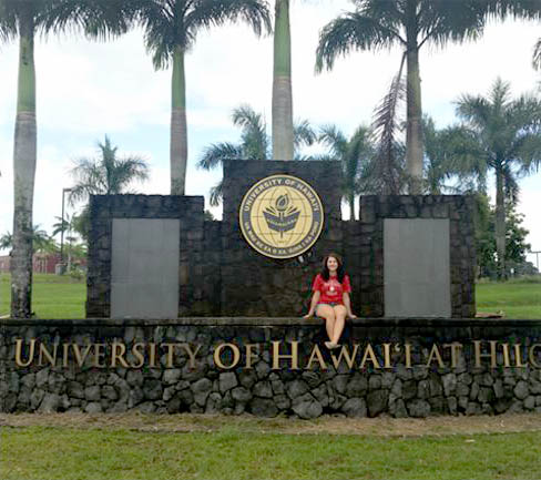 Student sitting on UH Hilo sign