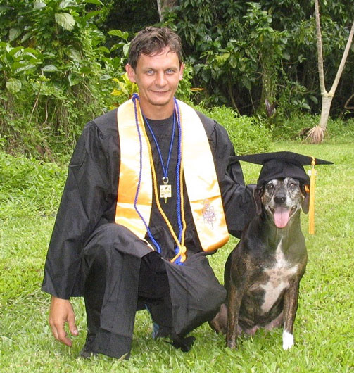 Student and dog in graduation gown