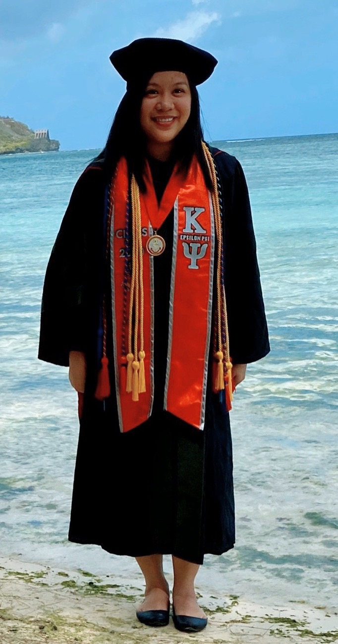 UH Hilo graduating student in cap and gown on the beach