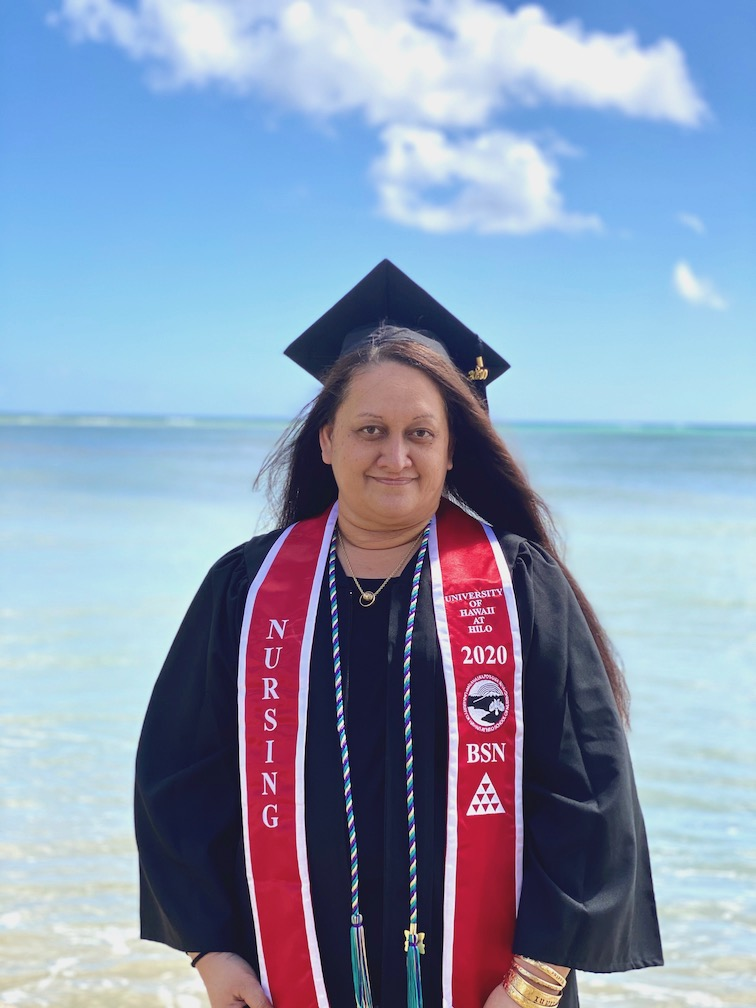 UH Hilo graduating nursing student in cap and gown at the beach