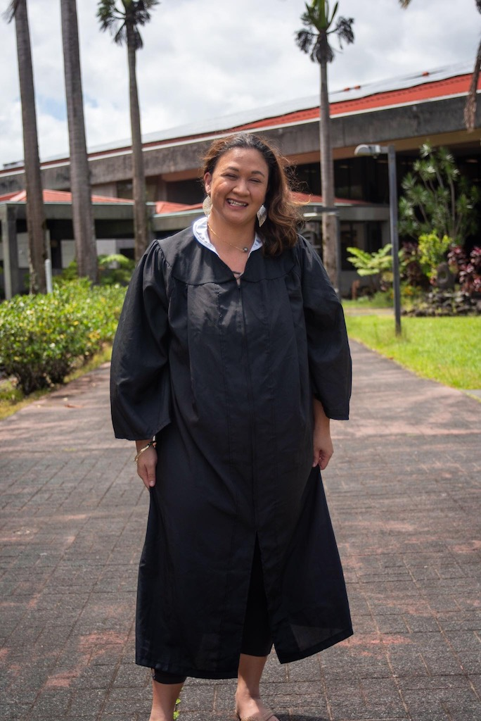 UH Hilo graduating student in gown winking