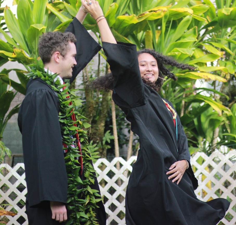 Two graduates in their gowns execute a dance manouver