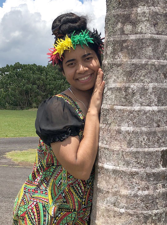 A studnet wearing a lei upon her head leans against a tree
