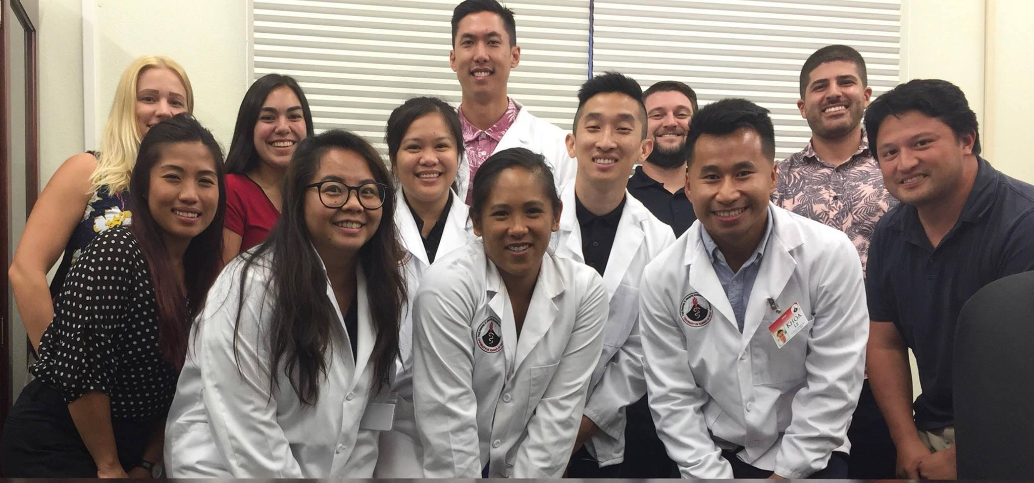 Pharmacy Students pose together in their lab coats.