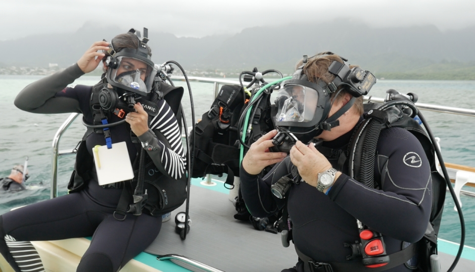 Two divers don mask on the back of a boat