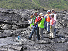 A crowd of students stands at a safe distance from a lava flow