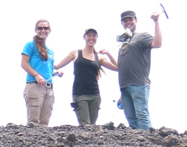 Three geologist stand with rock hammers raised