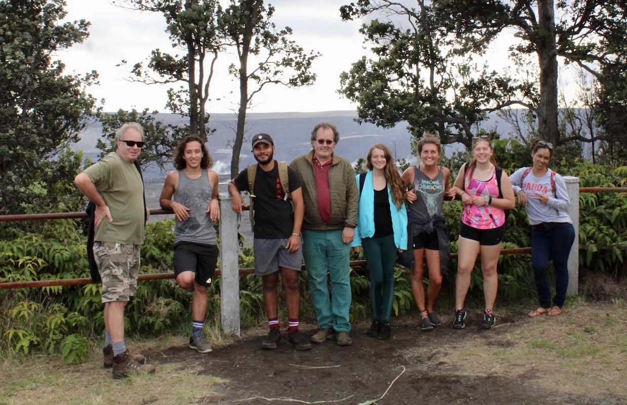 Seven students and professor stand in front of Kīlauea volcano crater