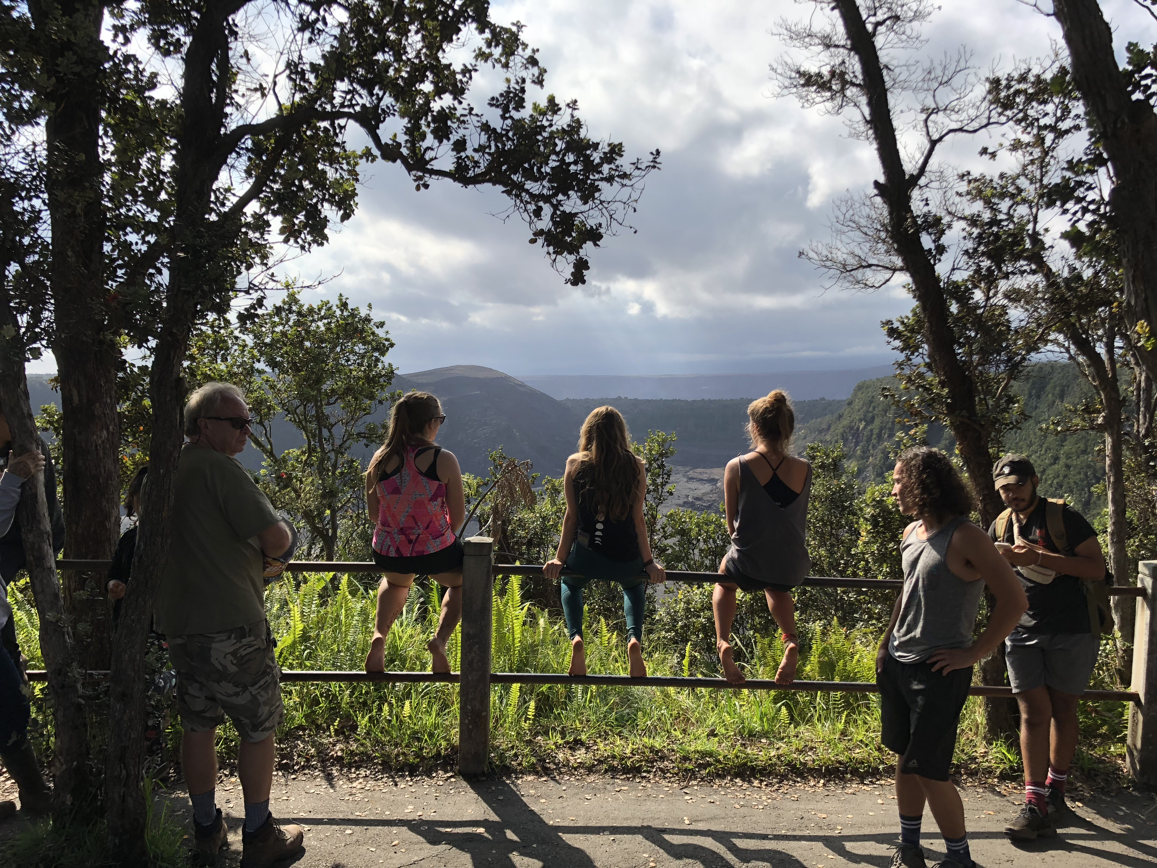 Three students sit on railing overlooking Kīlauea volcano crater while three students stand gazing