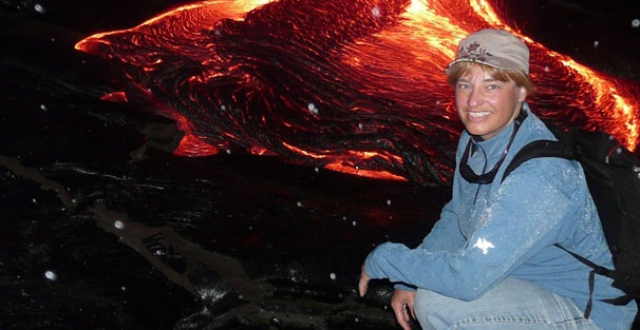 Donna Delparte kneeling next to an active lava flow