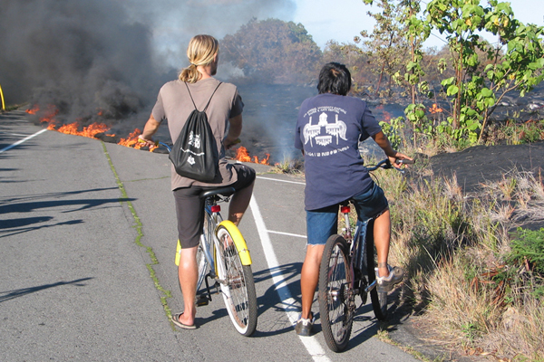 two residents on bicyles watch lava cover a roadway