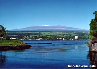 A snow-capped Maunakea can be seen from the beautiful Hilo Bay