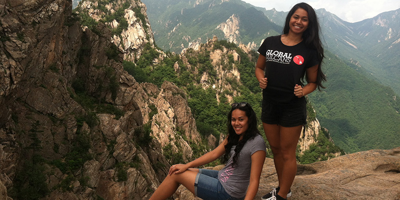 Students pose atop a wilderness cliff