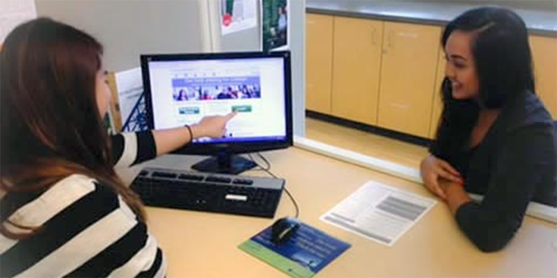 An advisor reviews information on the financial aid site with a student