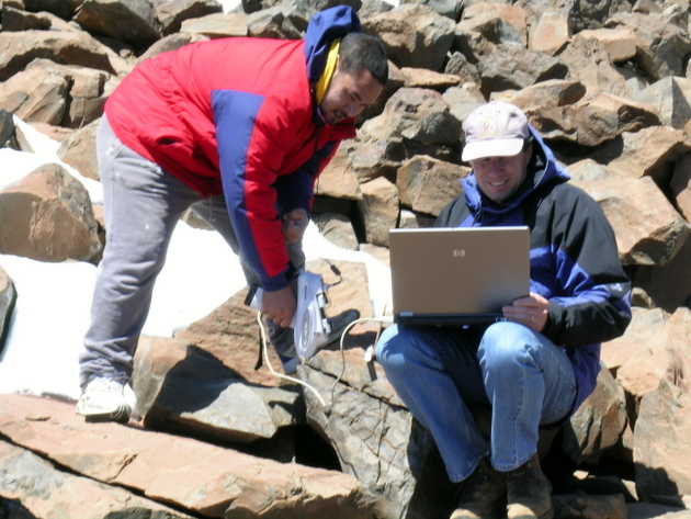 Peter Mills and student in a rock outcrop collect data on laptop.