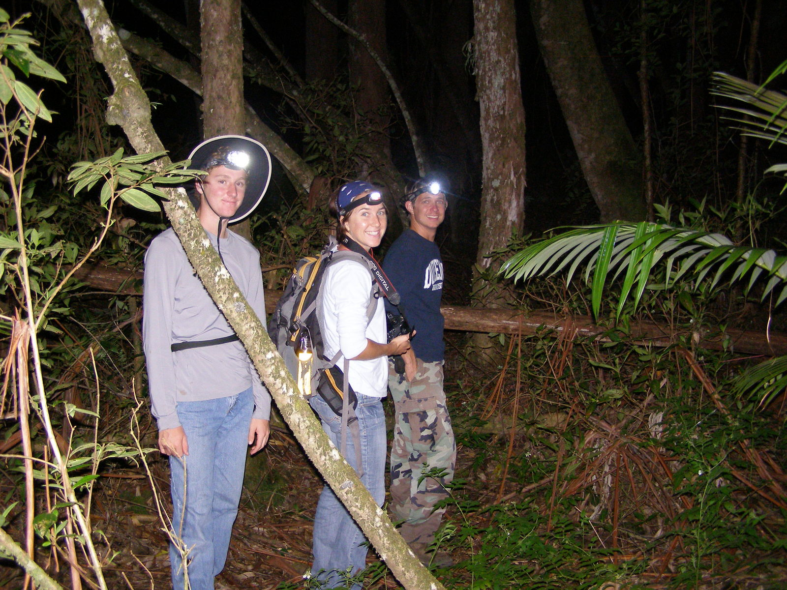 Three students in forest at night doing coqui research.