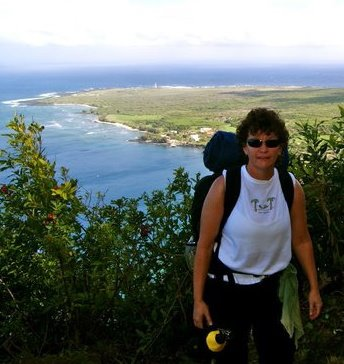 Kerri Inglis with back pack hiking up trail from Kaulapapa, peninsula in background.