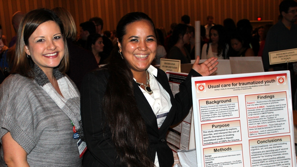 Associate Professor Charmaine Higa-McMillan (left) with student at poster display