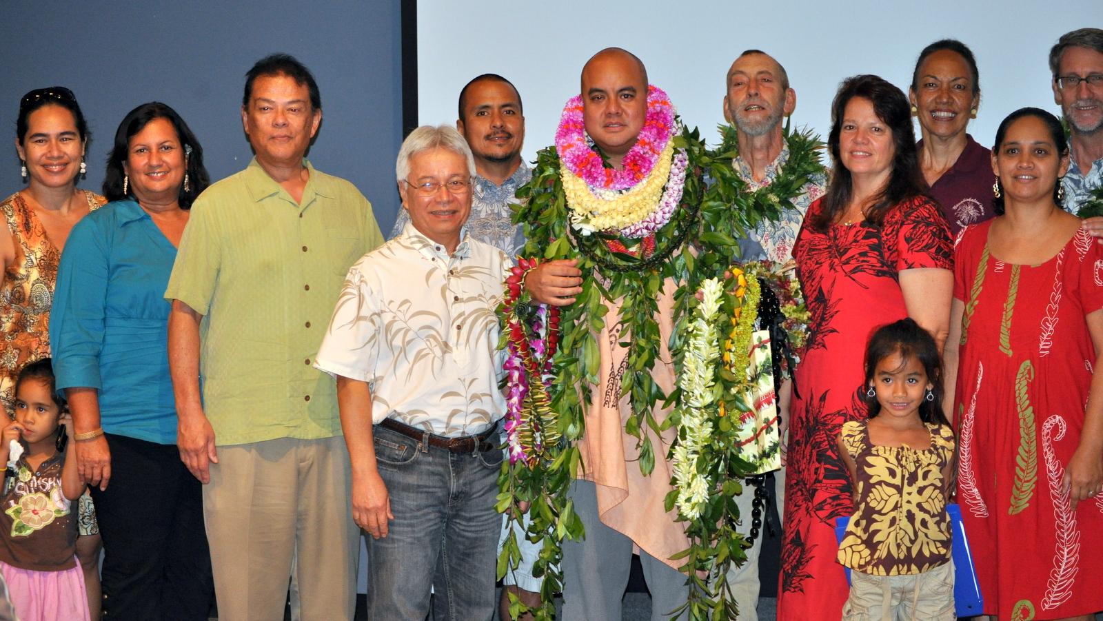 Hiapo with many lei standing with group of faculty and family.
