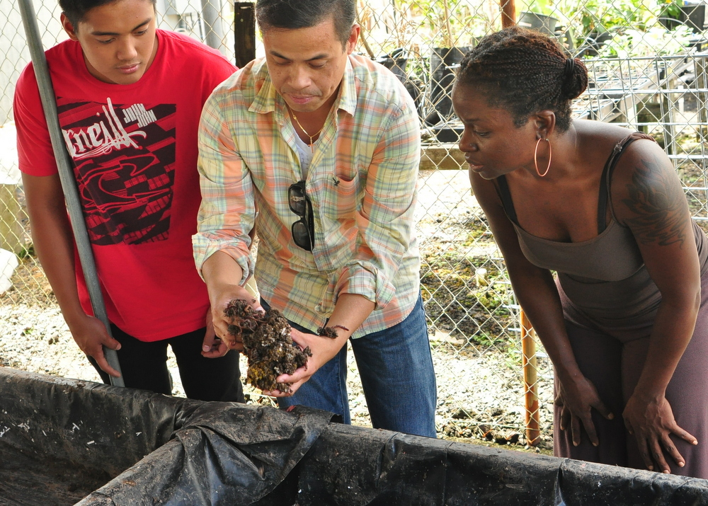 Norman Arancon showing two students soil material.