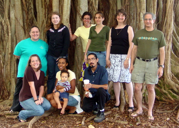 Dan Brown standing with his research team in front of huge banyan tree trunk.