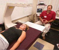 UH-Hilo student research assistant Mary Chapman, left, undergoes a full-body scan on the Hologic QDR-4500W bone densitometer, while exercise physiologist Linc Gotshalk looks on. The machine was donated to UHH by Dr. Doug Hiller, a Waimea orthopedic surgeon and sports doctor. – William Ing/Hawaii Tribune-Herald