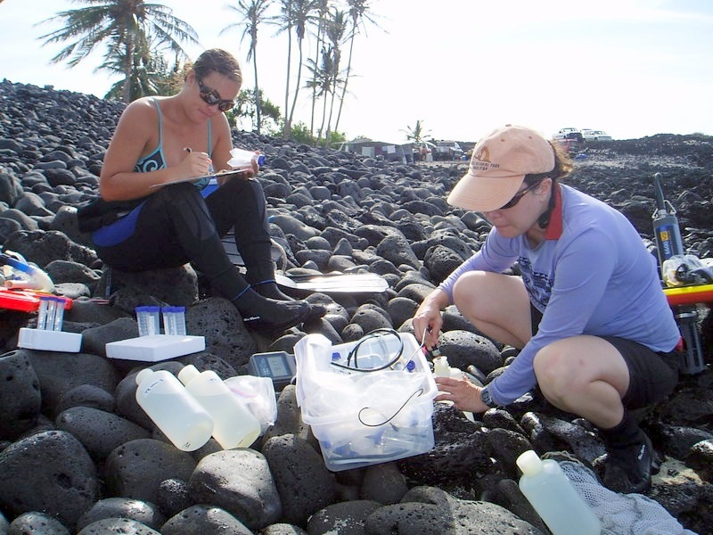Professor and student on rocky shoreline with equipment to sample water.