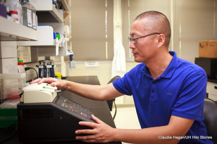 Li Tao working a piece of equipment in his lab.