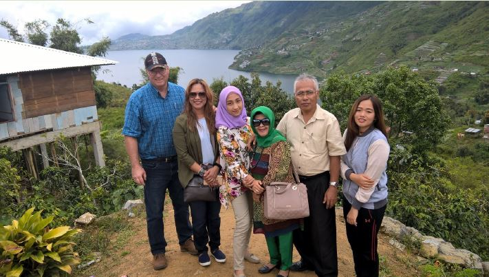 Group of people gathered for photo, background is beautiful landscape with sloping cliffs dropping off into water.