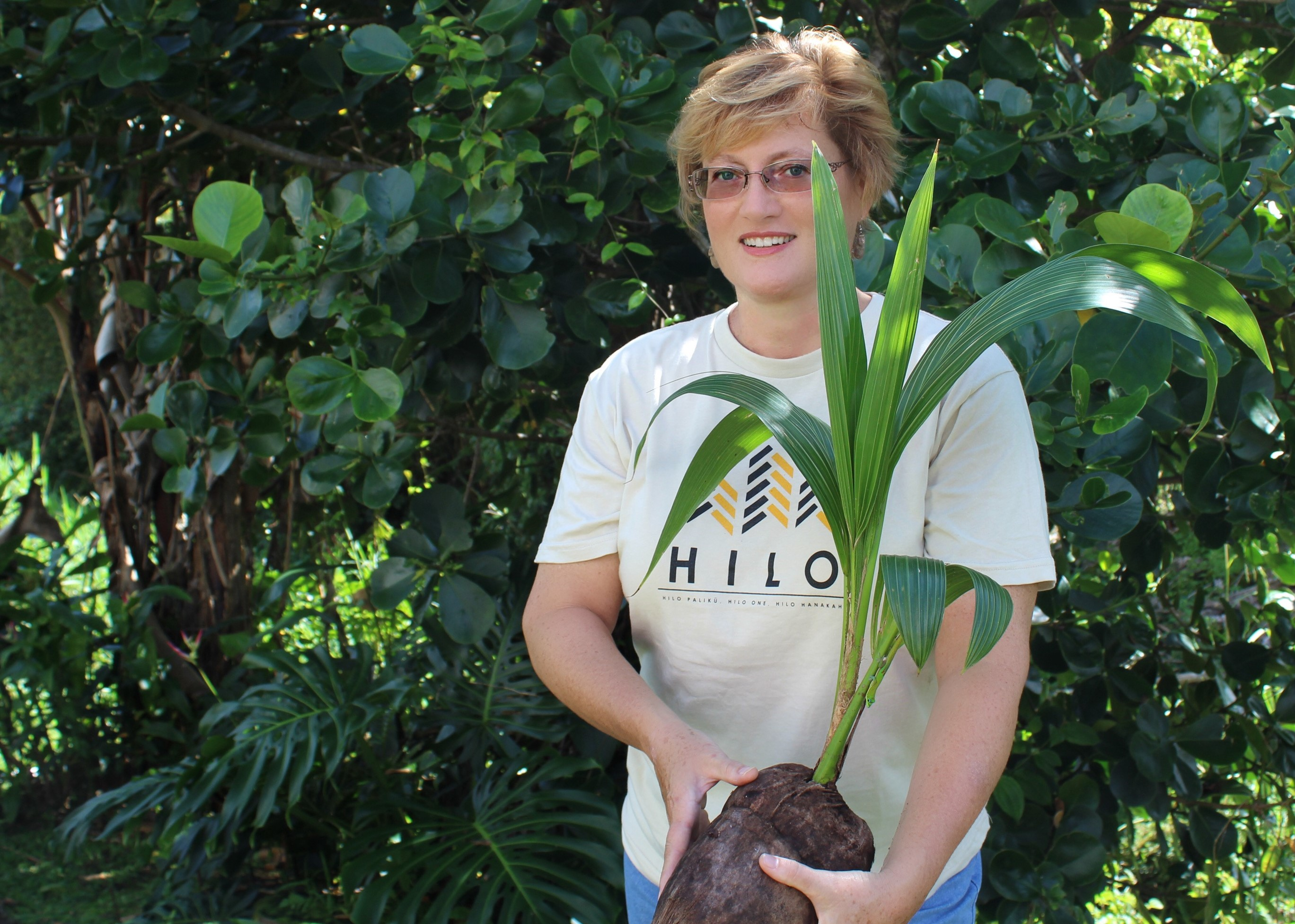 Brooke Hansen holding young coconut sprout.