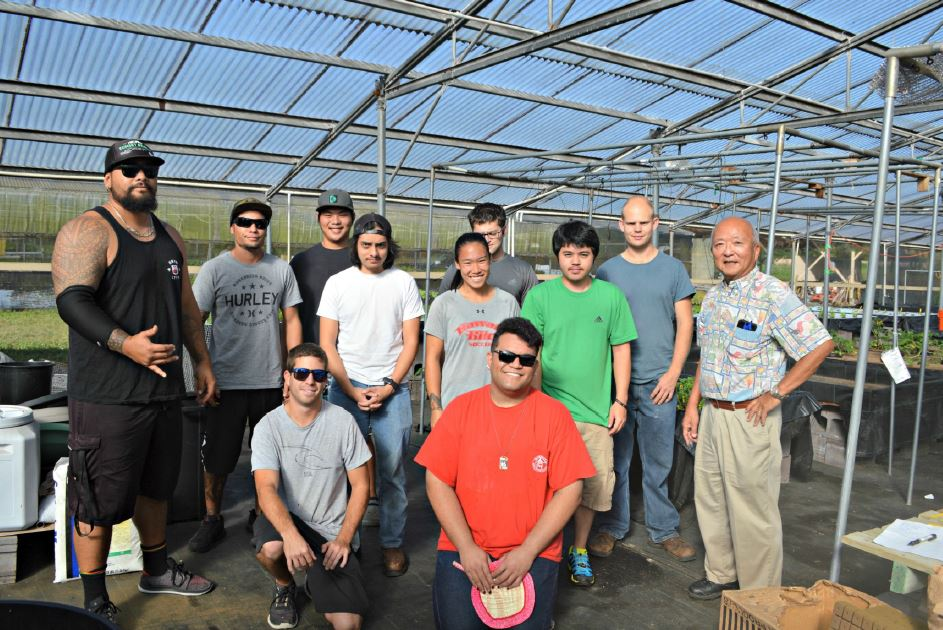 Group of students and faculty standing in greenhouse.
