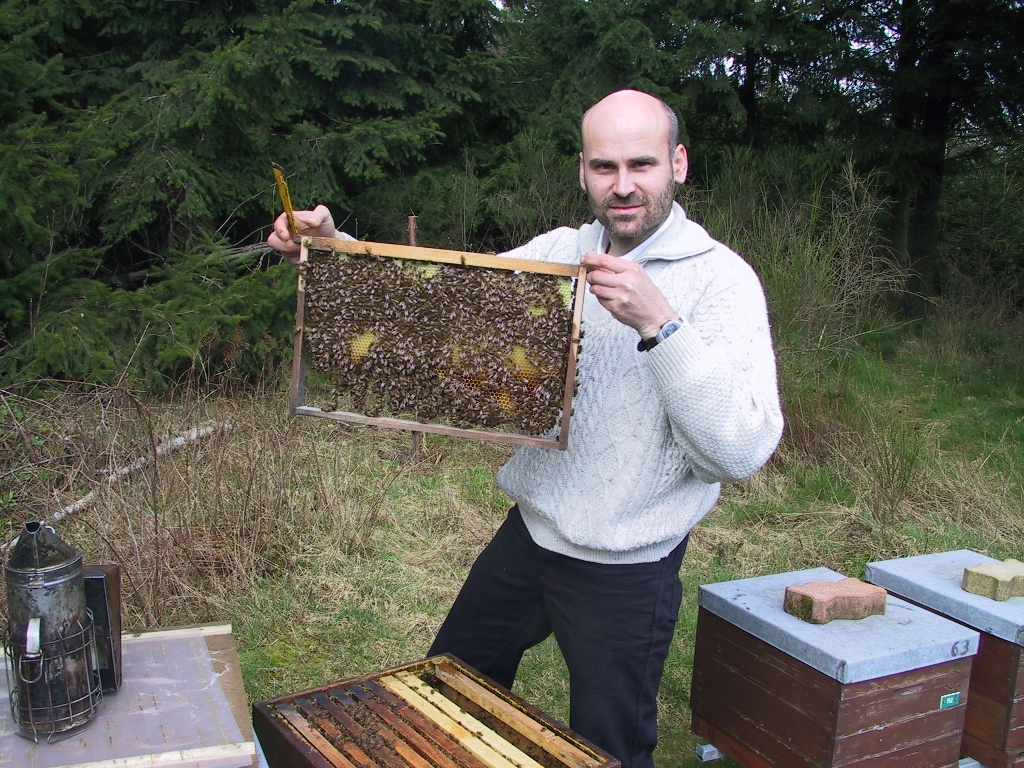 Harald Singer holds up a honeycomb while standing next to beeboxes.