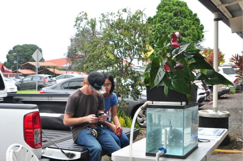 Two students sitting on the tailgate of a truck next to their tank display.