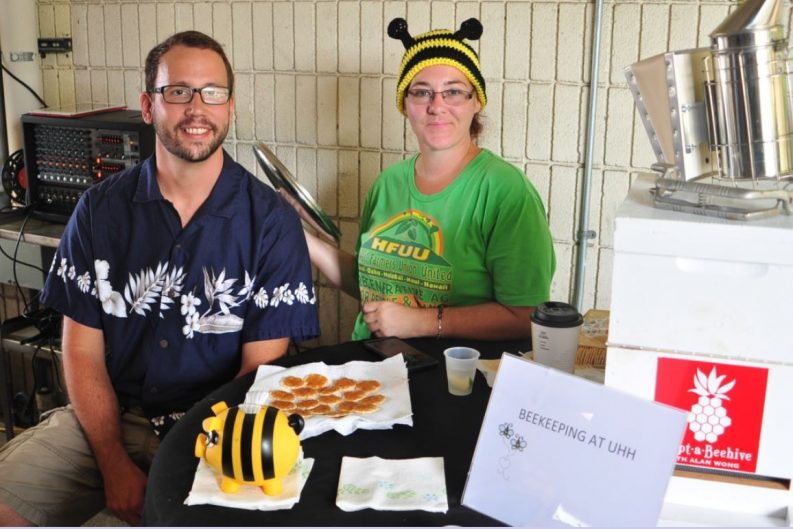 Two students at table about beekeeping. She has a bee hat on.