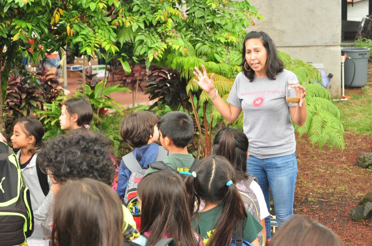 Student speaking to schoolchildren in the garden.