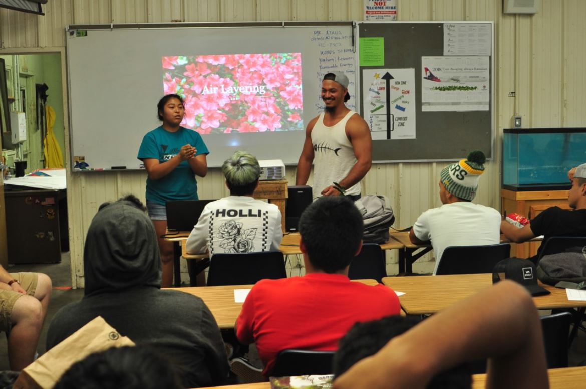 Two college students speak at the head of a class of students.