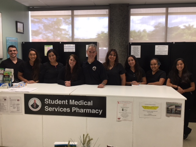 Three pharmacists stand behind a counter with a sign which reads UH Hilo Pharmacy